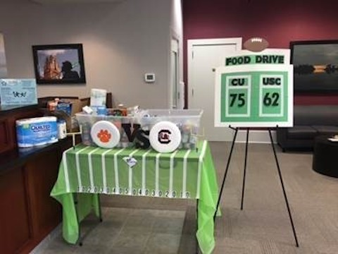 Two bins full of donated food have signs that designate Carolina or Clemson so people can donate in accordance to the team they prefer.