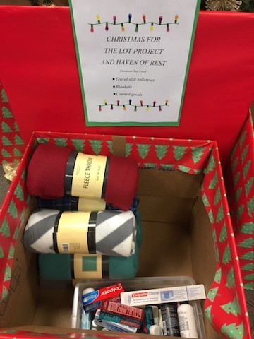 A box decorated with Christmas wrapping paper filled with donated toiletries.