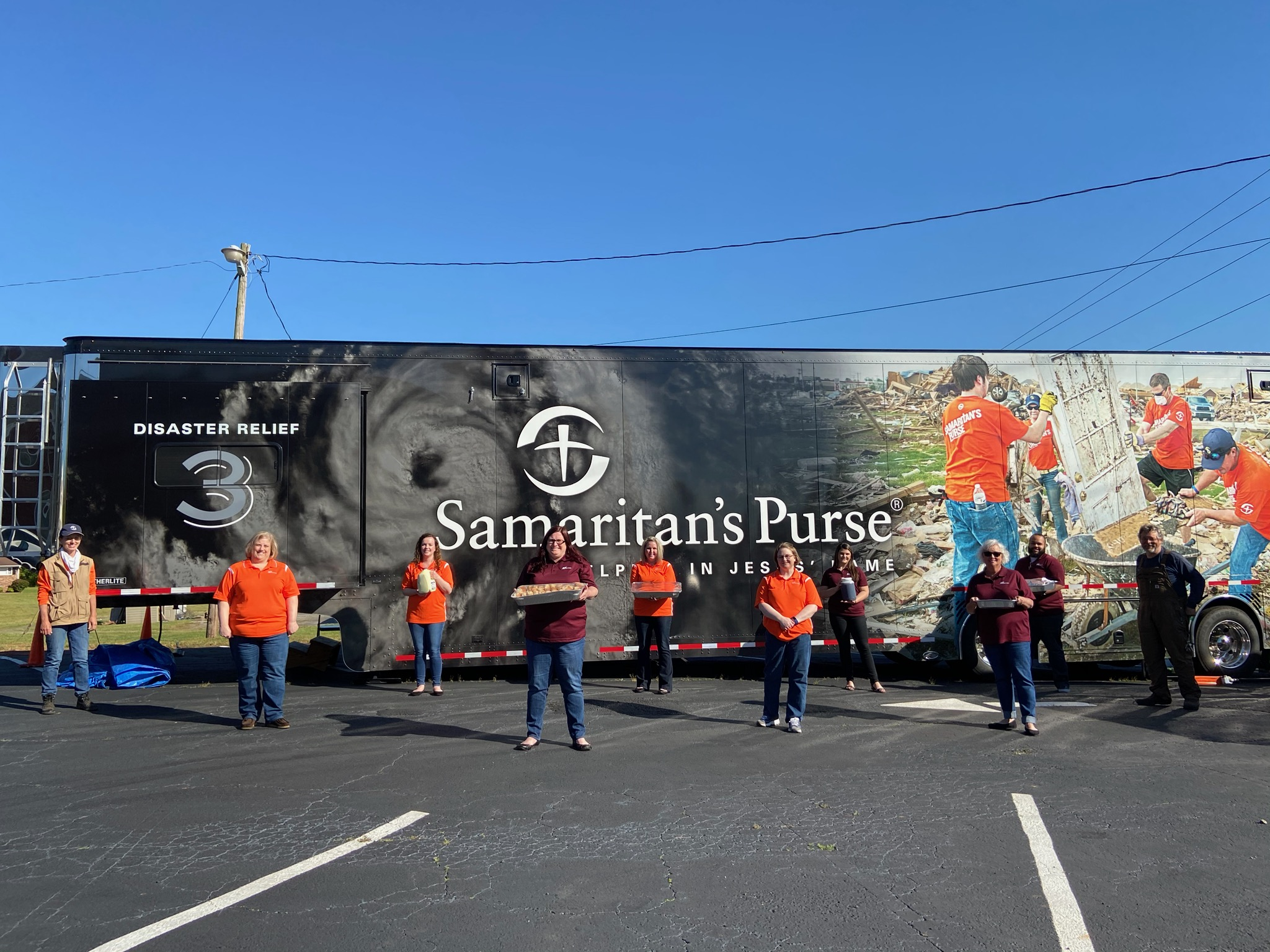 On a clear blue day, SCU staff stands spread out, holding up food supplies, alongside Samaritan's Purse volunteers in front of their large disaster relief van, reading number 3, in the church parking lot.
