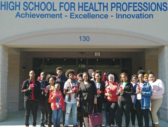 A smiling group of high school students outside their school building, with text that says High School for Health Professions Achievement - Excellence - Innovation