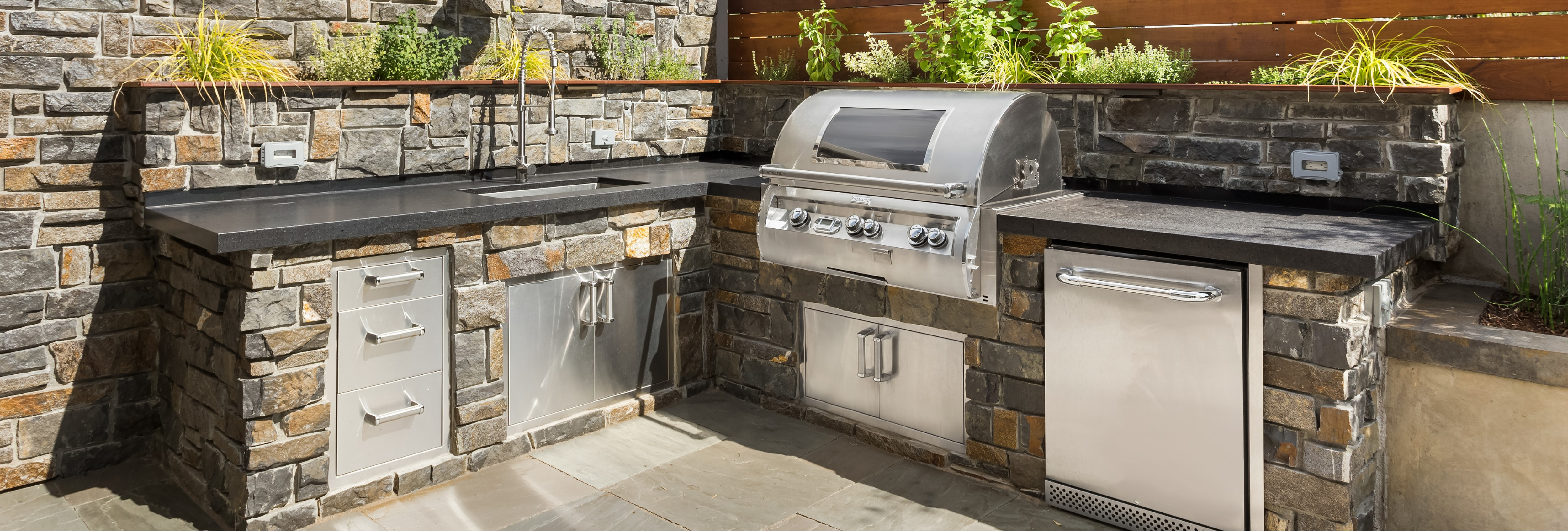 Outdoor kitchen with a large grill, sink and refrigerator